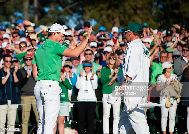 England's Danny Willett celebrates with his caddie Jonathan Smart on the 18th green during Round 4 of the 80th Masters Golf Tournament at the Augusta...