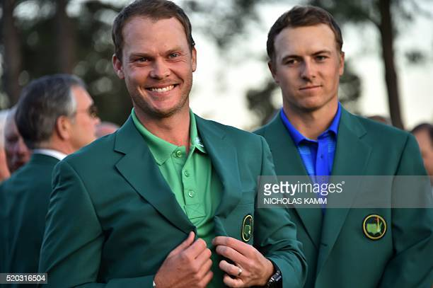 England's Danny Willett smiles wearing the Green Jacket as US golfer Jordan Spieth looks on at the end of the 80th Masters Golf Tournament at the...