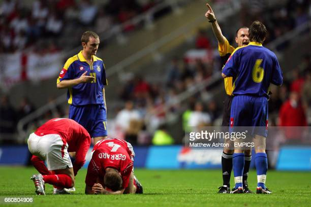 England's David Beckham checks on the injured Steven Gerrard as referee Michael McCurry orders Ukraines Oleh Shelayev away