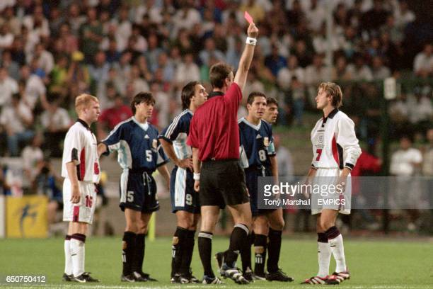 England's David Beckham is shown the red card by referee Kim Milton Neilsen for retaliating against Argentina's Diego Simeone