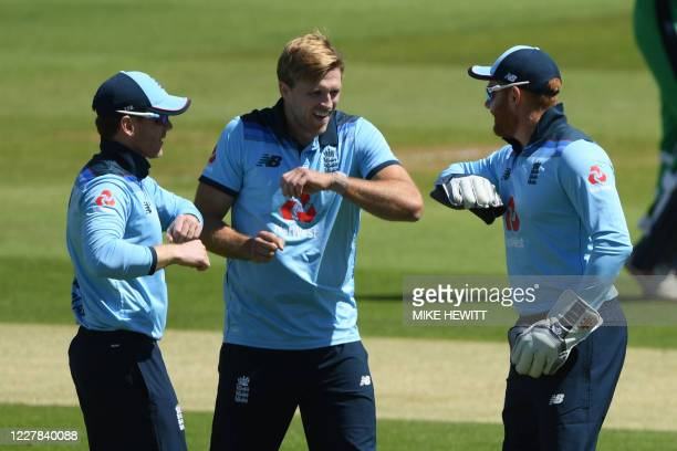 England's David Willey celebrates with England's Eoin Morgan after taking the wicket of Ireland's Paul Stirling during the first One Day...