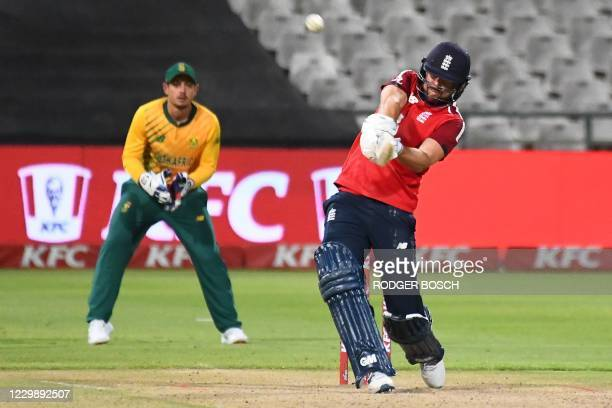 England's Dawid Malan hits a six as South Africa's captain and wicketkeeper Quinton de Kock looks on during the third T20 international cricket match...
