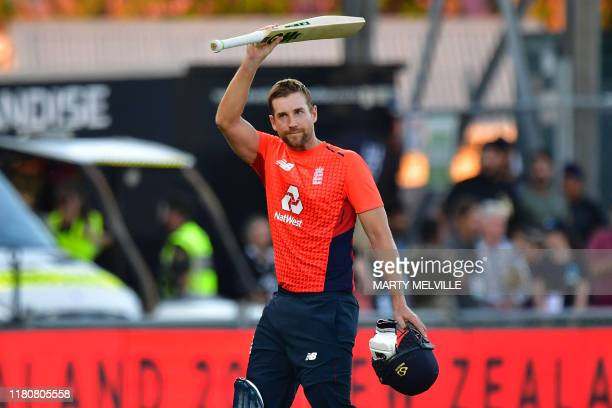 England's Dawid Malan lifts his bat as he walks from the field at the end of England's innings during the Twenty20 cricket match between New Zealand...