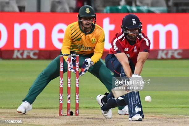 England's Dawid Malan plays a sweep shot as South Africa's captain and wicketkeeper Quinton de Kock looks on during the third T20 international...
