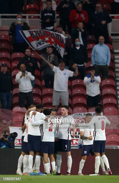 England's defender Bukayo Saka is mobbed by teammates after scoring the opening goal during the international friendly football match between England...