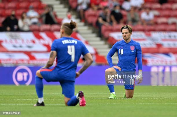 England's defender Declan Rice and England's striker Jack Grealish 'take a knee' ahead of the international friendly football match between England...