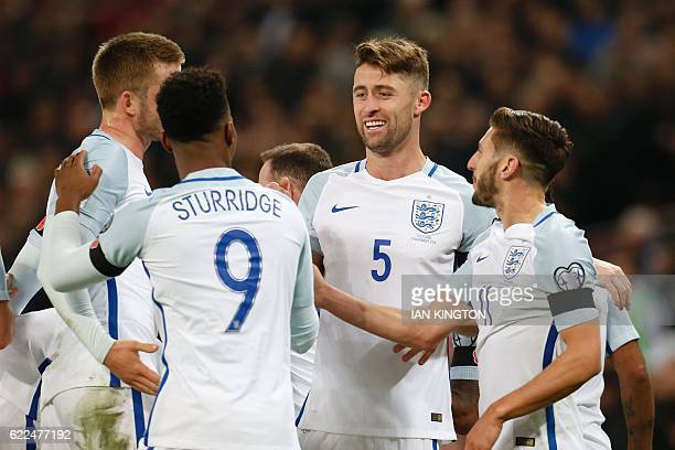 England's defender Gary Cahill celebrates with teammates after scoring their third goal during a World Cup 2018 qualification match between England...