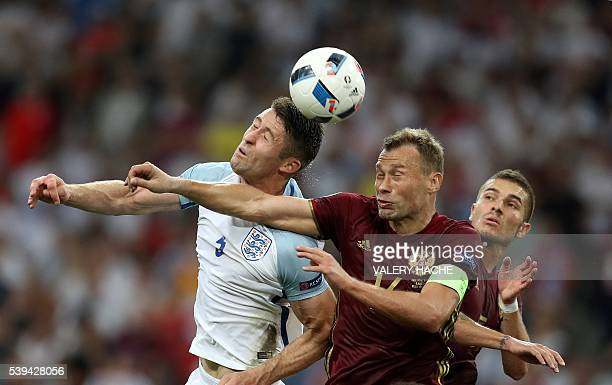 TOPSHOT England's defender Gary Cahill vies with Russia's defender Vasily Berezutskiy during the Euro 2016 group B football match between England and...