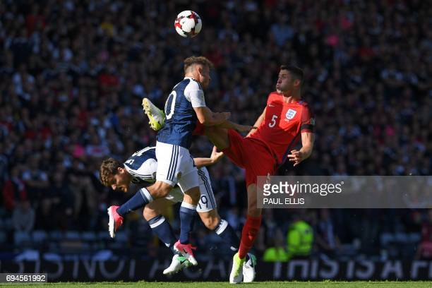 England's defender Gary Cahill vies with Scotland's striker Chris Martin and Scotland's midfielder Ryan Fraser during the group F World Cup...