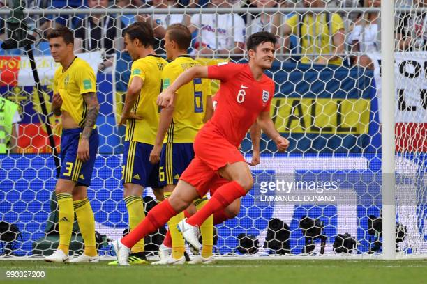 England's defender Harry Maguire celebrates after scoring the opener during the Russia 2018 World Cup quarterfinal football match between Sweden and...