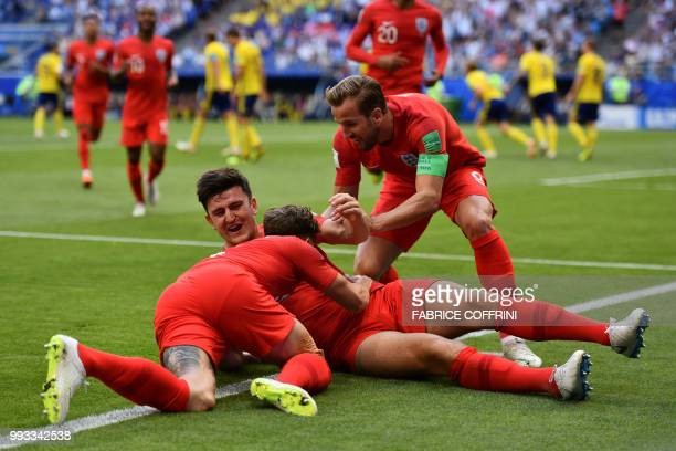 England's defender Harry Maguire celebrates with England's forward Harry Kane and a teammate after scoring the opener during the Russia 2018 World...