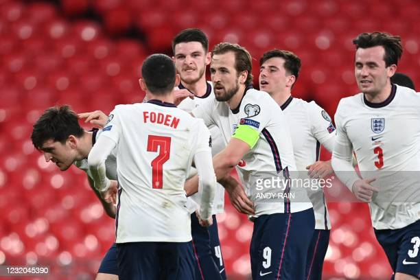 England's defender Harry Maguire celebrates with team-mates after scoring their second goal during the FIFA World Cup Qatar 2022 Group I...