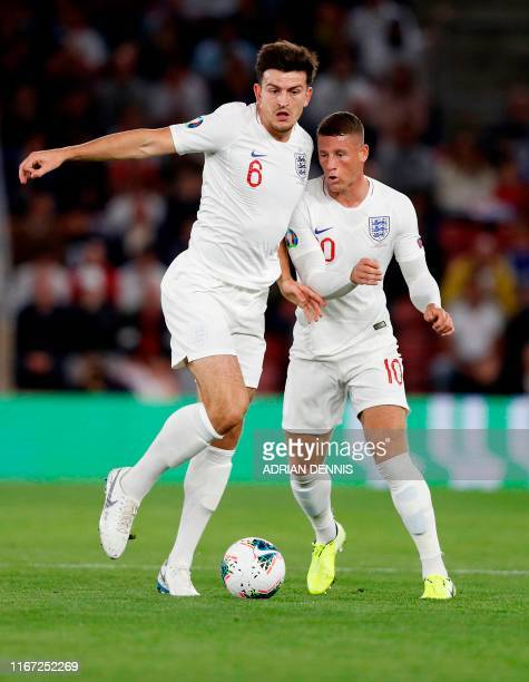 England's defender Harry Maguire clashes with England's midfielder Ross Barkley during the UEFA Euro 2020 qualifying Group A football match between...