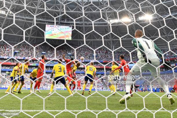 England's defender Harry Maguire heads the ball to score the opener during the Russia 2018 World Cup quarterfinal football match between Sweden and...
