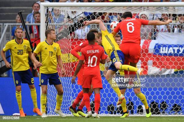 TOPSHOT England's defender Harry Maguire heads to score the opener during the Russia 2018 World Cup quarterfinal football match between Sweden and...