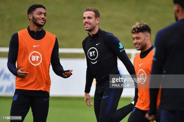 England's defender Joe Gomez England's midfielder Jordan Henderson and England's midfielder Alex OxladeChamberlain attend an England team training...