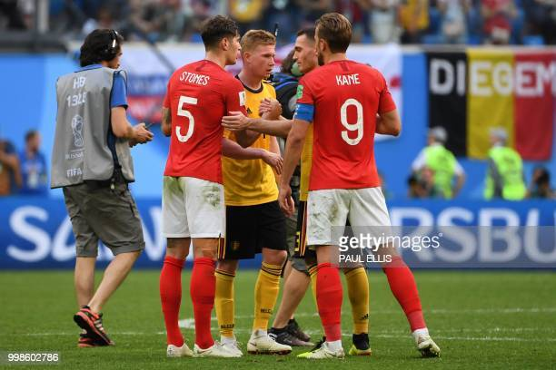 England's defender John Stones and England's forward Harry Kane shake hands with Belgium's midfielder Kevin De Bruyne and Belgium's defender Thomas...