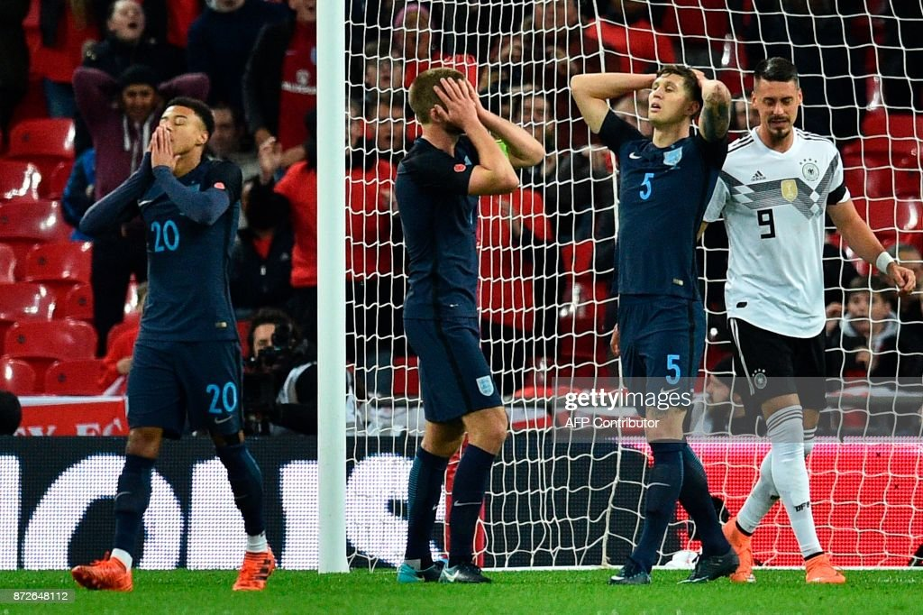 England's defender John Stones (3L) and England's midfielder Jesse Lingard (L) react after England's midfielder Jesse Lingard missed a late chance during the friendly international football match between England and Germany at Wembley Stadium in London on November 10, 2017. / AFP PHOTO / Glyn KIRK / NOT