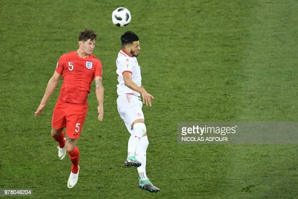 England's defender John Stones jumps for the ball with Tunisia's forward Anice Badri during the Russia 2018 World Cup Group G football match between...