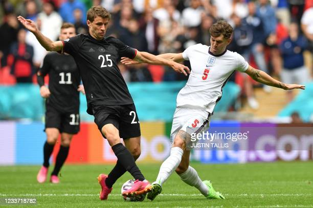 England's defender John Stones vies for the ball with Germany's forward Thomas Mueller during the UEFA EURO 2020 round of 16 football match between...