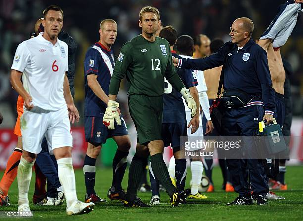 England's defender John Terry and a member of medical staff comfort goalkeeper Robert Green at the end of their 2010 World Cup group C first round...