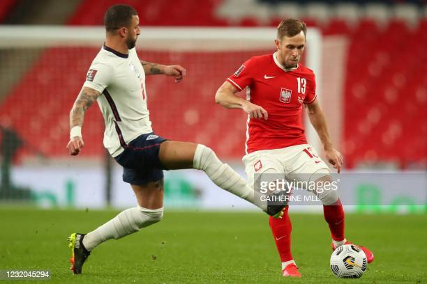 England's defender Kyle Walker challenges Poland's defender Maciej Rybus during the FIFA World Cup Qatar 2022 Group I qualification football match...