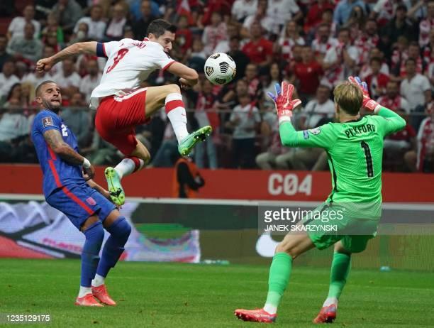 England's defender Kyle Walker , England's goalkeeper Jordan Pickford and Poland's forward Robert Lewandowski vie for the ball during the FIFA World...