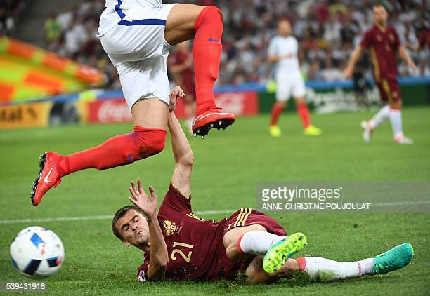 TOPSHOT England's defender Kyle Walker jumps over a tackle by Russia's defender Georgi Shchennikov during the Euro 2016 group B football match...