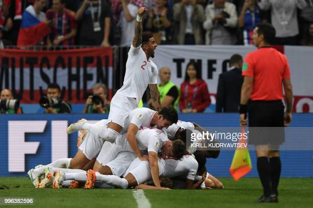England's defender Kyle Walker jumps over teammates as they celebrate after scoring a goal during the Russia 2018 World Cup semi-final football match...