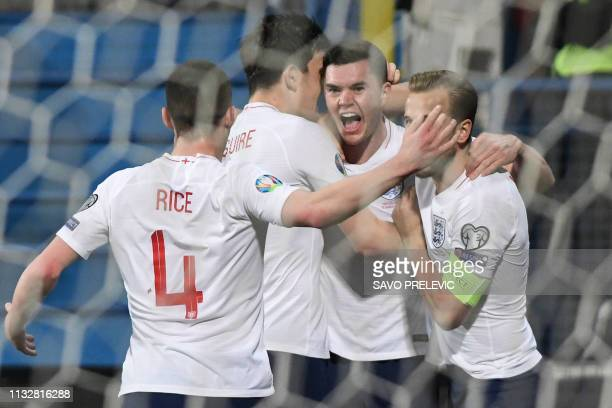 England's defender Michael Keane is congratulated by teammates after scoring a goal during the Euro 2020 football qualification match between...