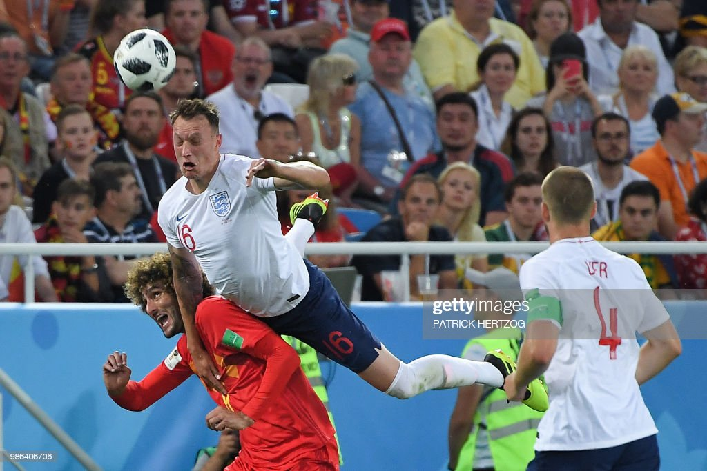 TOPSHOT - England's defender Phil Jones (top) jumps on Belgium's midfielder Marouane Fellaini during the Russia 2018 World Cup Group G football match between England and Belgium at the Kaliningrad Stadium in Kaliningrad on June 28, 2018. (Photo by Patrick HERTZOG / AFP) / RESTRICTED