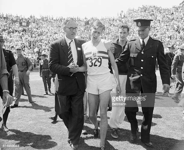 England's Dr. Roger Bannister, , is escorted from the field here after winning the mile race in the British Empire Games at Vancouver. Bannister's...