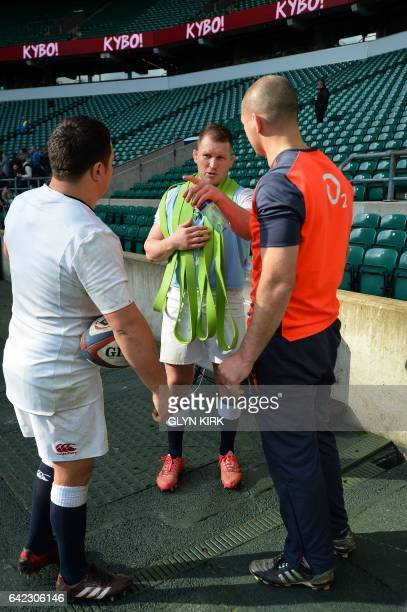 England's Dylan Hartley talks to hooker Jamie George and coach Steve Borthwick during an England rugby team training session at Twickenham stadium in...