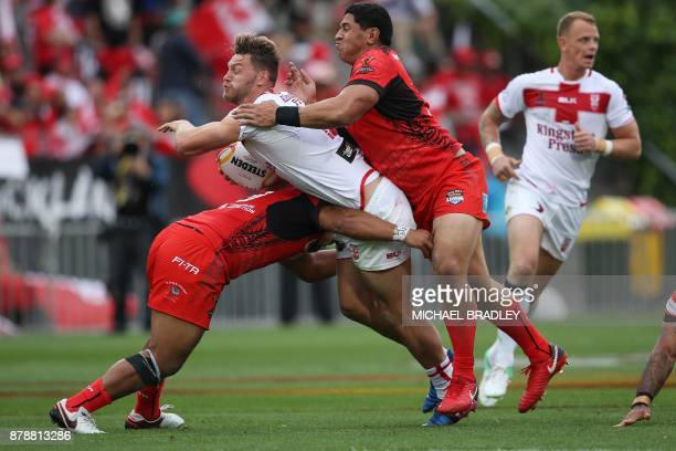 England's Elliott Whitehead is tackled by Tonga's defence during the Rugby League World Cup men's semifinal match between Tonga and England at Mt...
