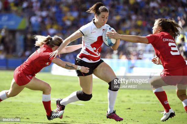 England's Emily Scarratt is tackled by Canada's Kayla Moleschi and Caroline Crossley in the women's rugby sevens bronze medal match at the Robina...