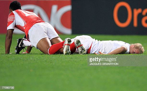 England's flanker Lewis Moody lies on the pitch next to Tonga's fullback Vungakoto Lilo during the rugby union World Cup group A match England vs...