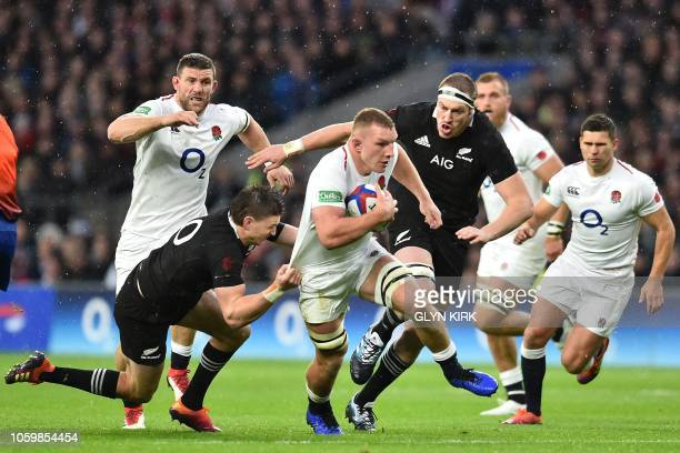 England's flanker Sam Underhill is tackled by New Zealand's flyhalf Beauden Barrett during the autumn international rugby union match between England...