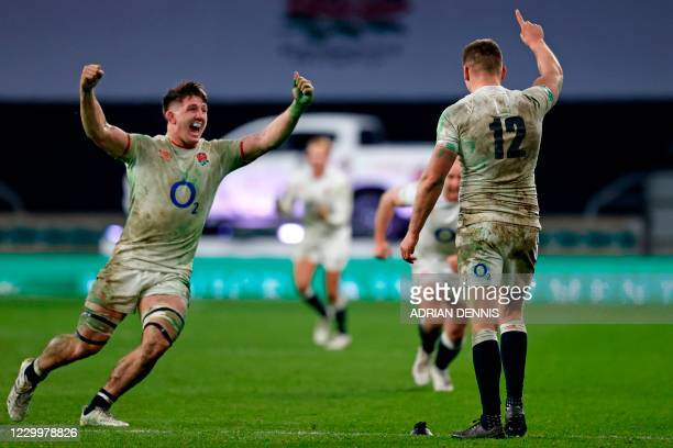 England's flanker Tom Curry runs to celebrate with England's centre Owen Farrell after he kicks a penalty in extra-time to win the final of the...