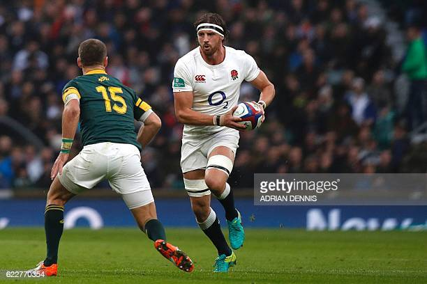 England's flanker Tom Wood passes the ball by South Africa's full-back Willie le Roux during the rugby union test match between England and South...
