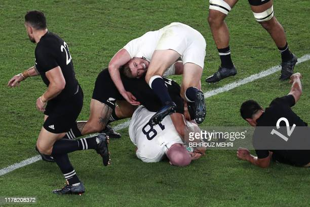 England's fly-half Owen Farrell is tackled during the Japan 2019 Rugby World Cup semi-final match between England and New Zealand at the...
