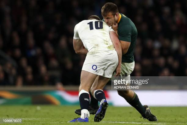 England's flyhalf Owen Farrell makes a dubious tackle on South Africa's Andre Esterhuizen late in the game which is looked at by officials during the...