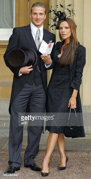 England's football captain David Beckham stands with his wife Victoria as he shows off the OBE he received 27 November from Britain's Queen Elizabeth...