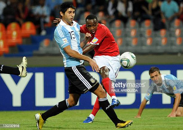 England's footballer Saido Berahino shoots the ball in front of Argentina's Alan Ruiz during a FIFA Under20 World Cup football match held at the...