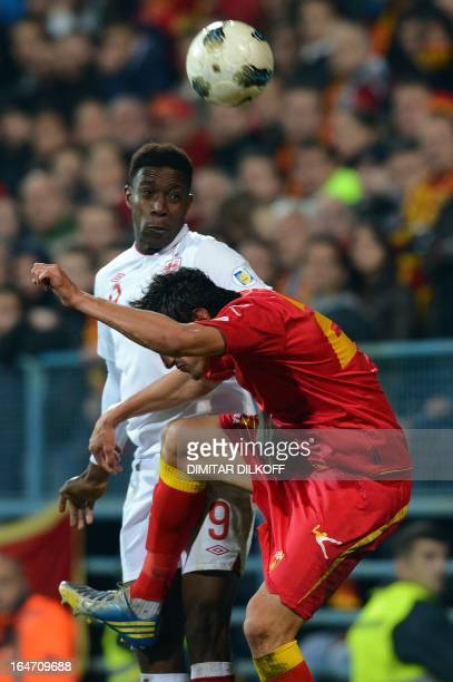 England's forward Danny Welbeck jumps for the ball with Montenegro's defender Stefan Savic during their World Cup 2014 qualification match at...