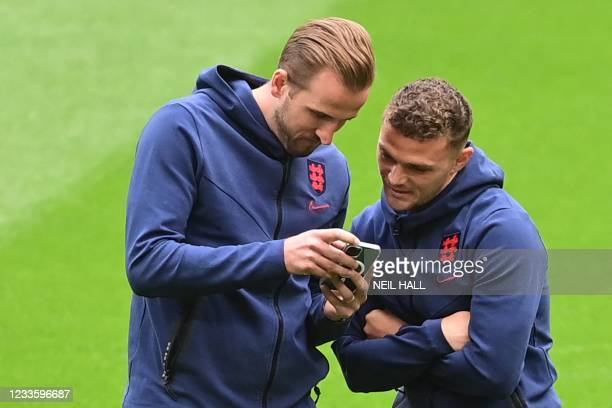 England's forward Harry Kane and England's defender Kieran Trippier look at Kane's phone prior to the UEFA EURO 2020 Group D football match between...
