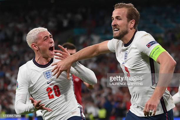 England's forward Harry Kane celebrates with England's midfielder Phil Foden after scoring a goal during the UEFA EURO 2020 semi-final football match...
