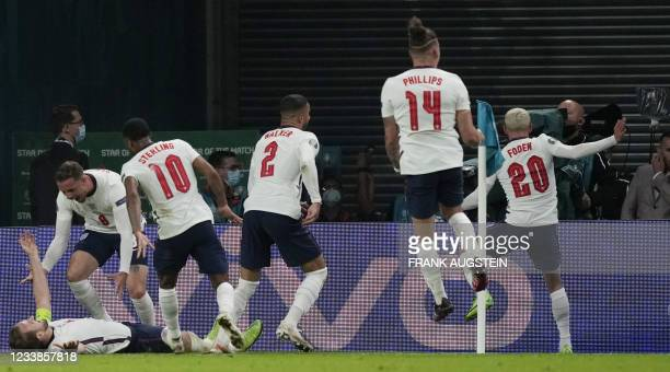 England's forward Harry Kane celebrates with teammates after scoring a penalty kick during the UEFA EURO 2020 semi-final football match between...
