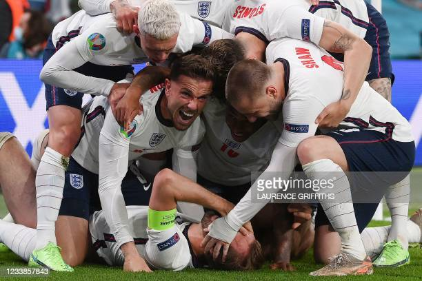 England's forward Harry Kane celebrates with teammates after scoring a goal during the UEFA EURO 2020 semi-final football match between England and...