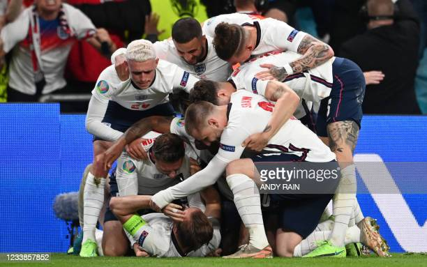 England's forward Harry Kane celebrates with teammates after scoring a penalty kick and his team's second goal during the UEFA EURO 2020 semi-final...