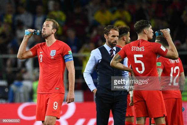 England's forward Harry Kane drinks water next to teammates and England's coach Gareth Southgate before the start of the extratime during the Russia...